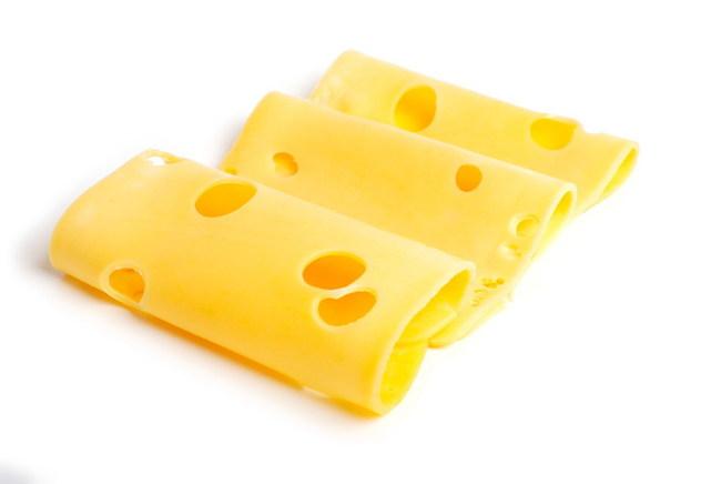 Пластинки нарезанного сыра с дырками. Фото
