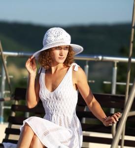 Молодая красивая девушка в белом платье и белой шляпке на море