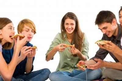 Молодые люди едят пиццу